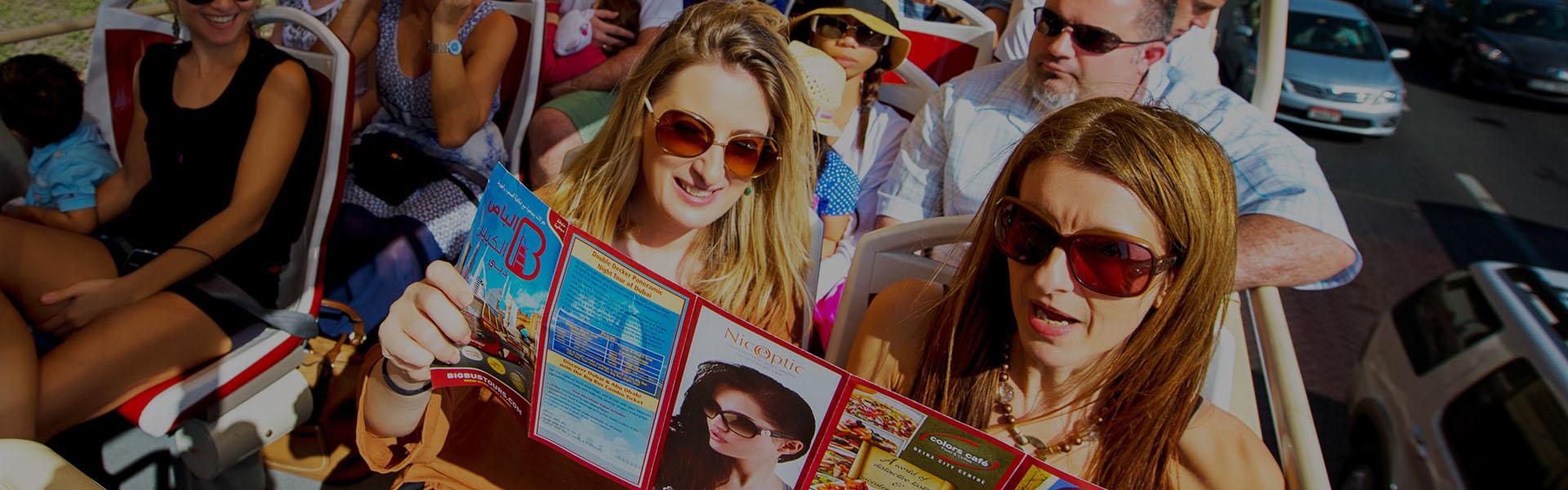 Touristen sehen sich die Karte von Big Bus Dubai an