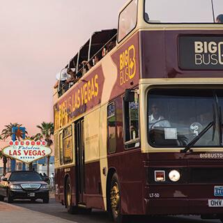 Big Bus Passing Las Vegas Sign