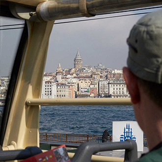 Tourists on bus looking at Galata Tower