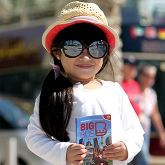 Mädchen mit Big Bus Abu Dhabi Informationsbroschüre