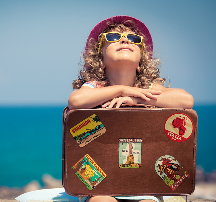 Child ready to travel with suitcase