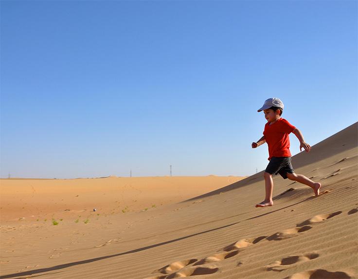 Junge läuft auf Sanddünen