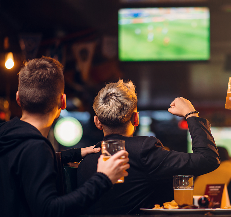 Friends drinking and watching sport in a bar