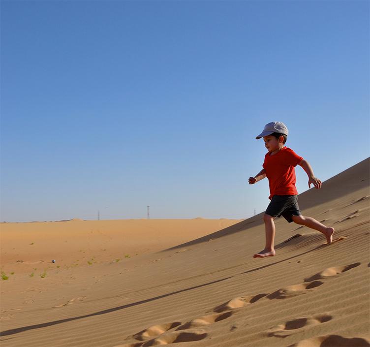 Junge rennt über Sanddünen in Abu Dhabi