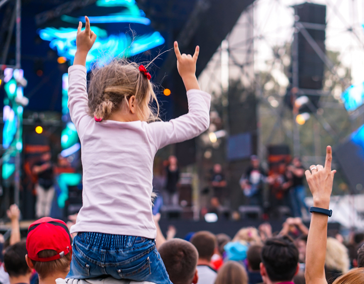 Girl on her dad's shoulders watching a festival