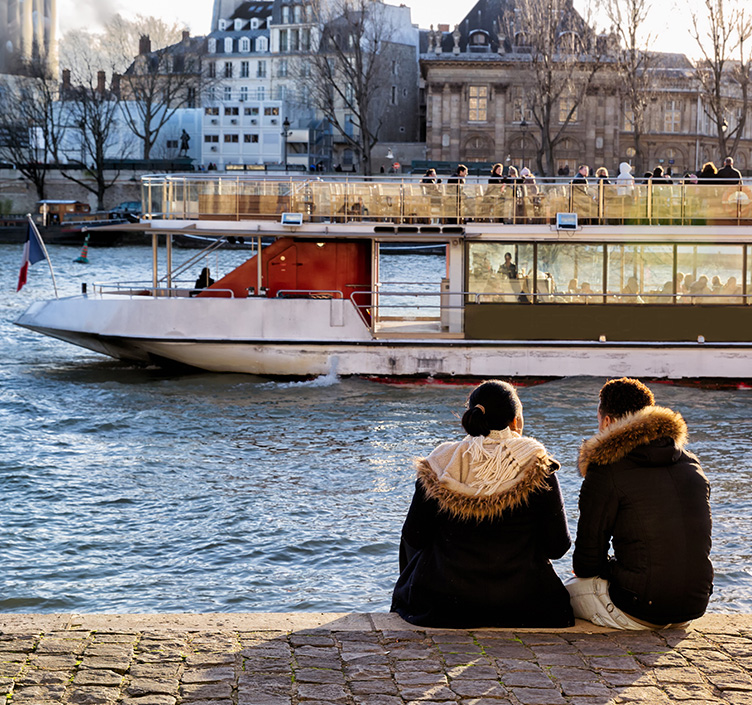 Couple watching a boat go down The Seine