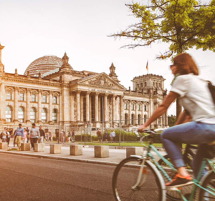 Lady cycling past the Reichstag