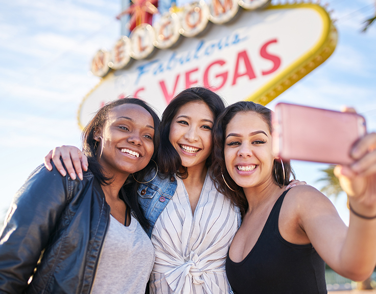 Friends taking selfie in front of Las Vegas sign