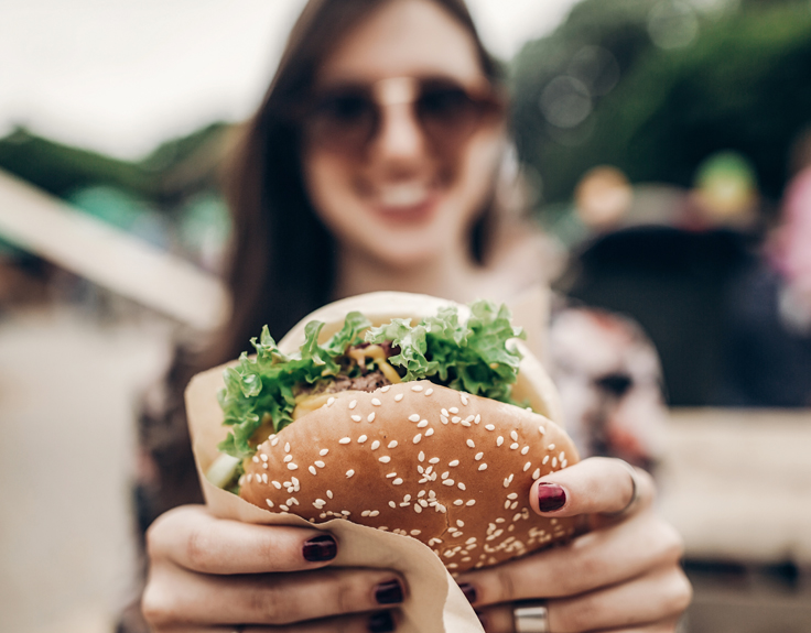 Girl smiling and holding out a burger