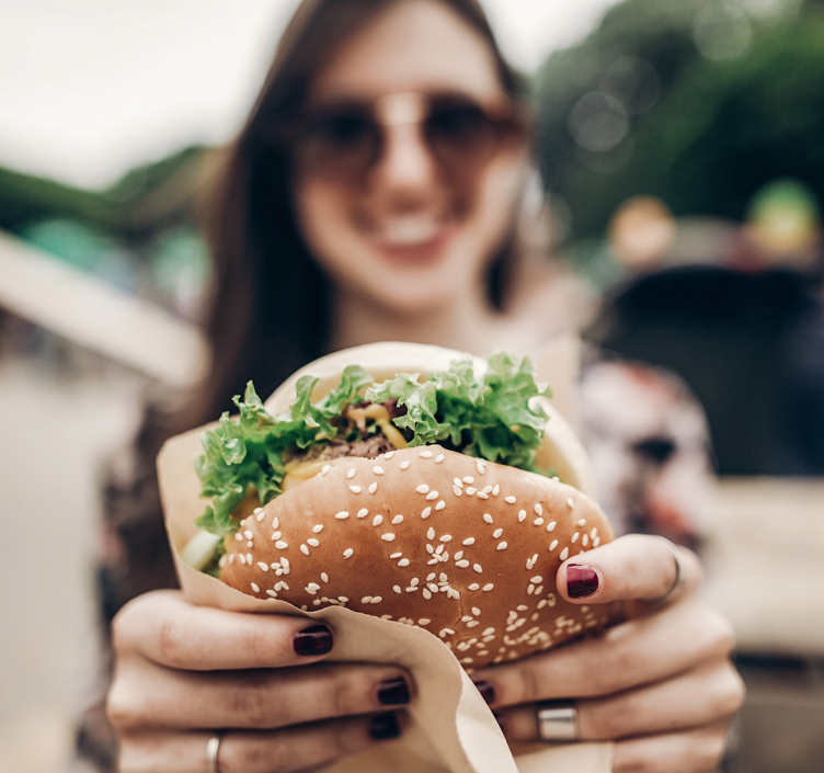 Lady eating a burger at a food festival