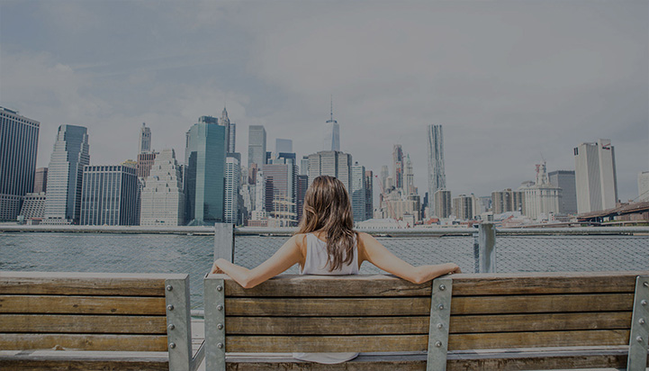 Girl on a bench looking at New York Skyline