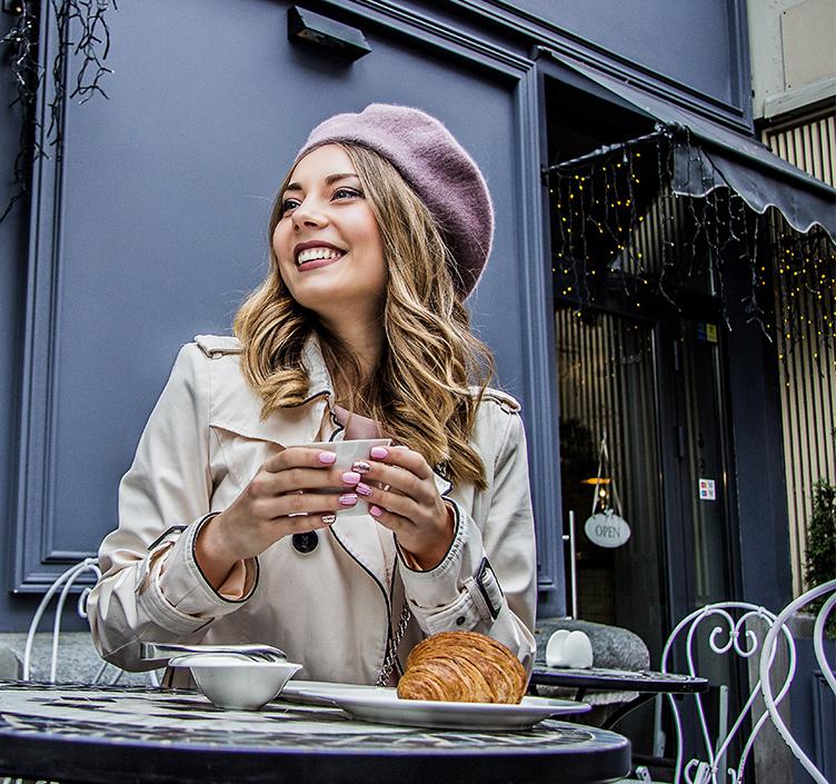 Lady drinking coffee in a Parisian coffee shop
