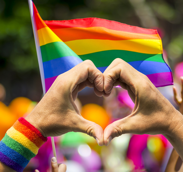 Pride rainbow flag with man holding his hands in a heart shape