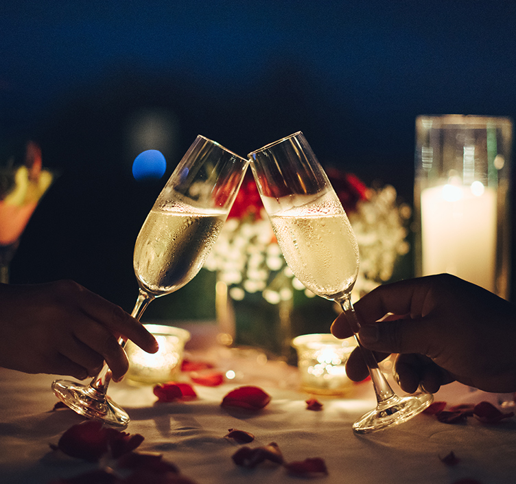 Candlelit dinner, couple cheering a glass of champagne