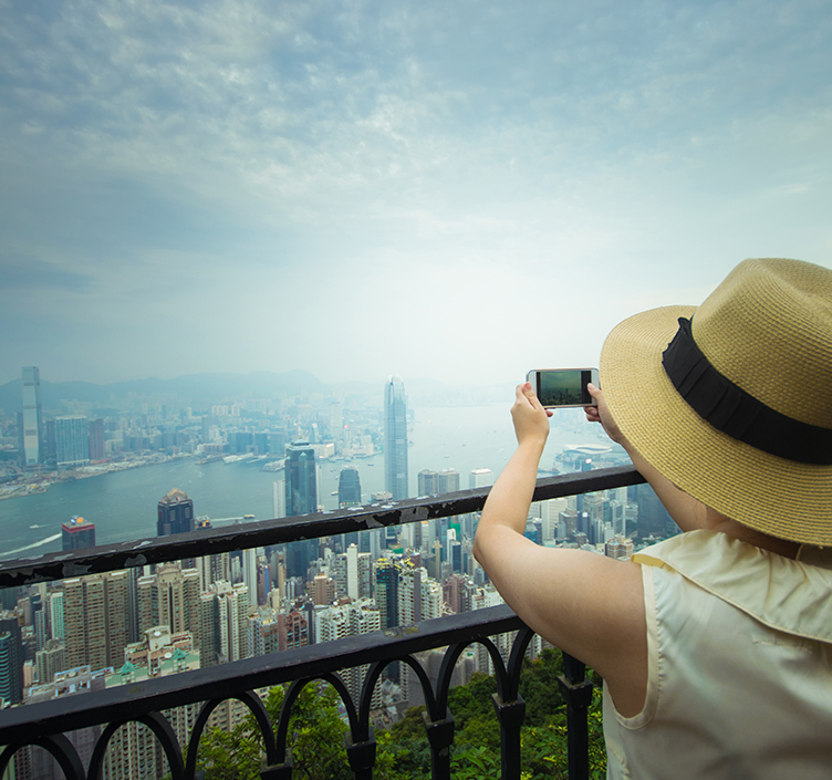 Lady taking picture of Hong Kong skyline