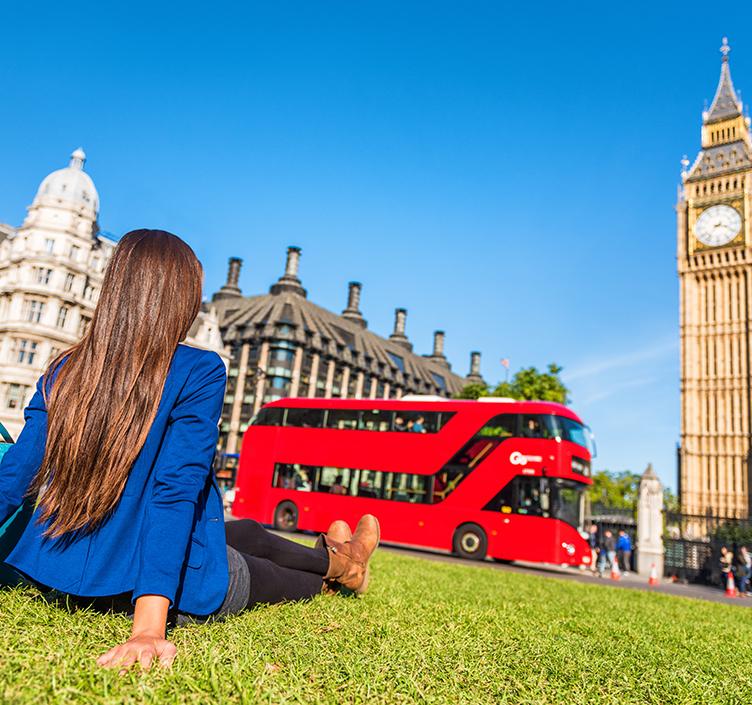 Girl watching red bus drive past Big Ben
