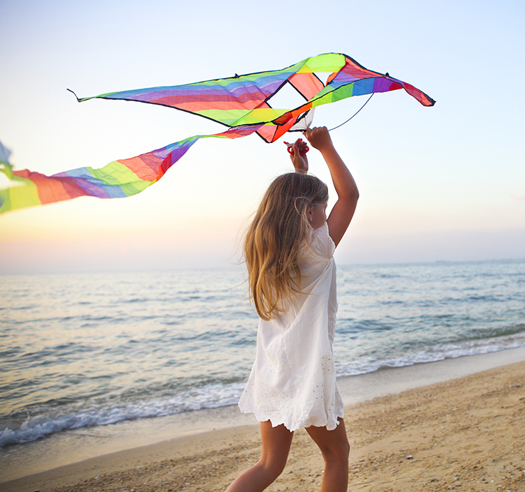 Girl flying kite on the beach