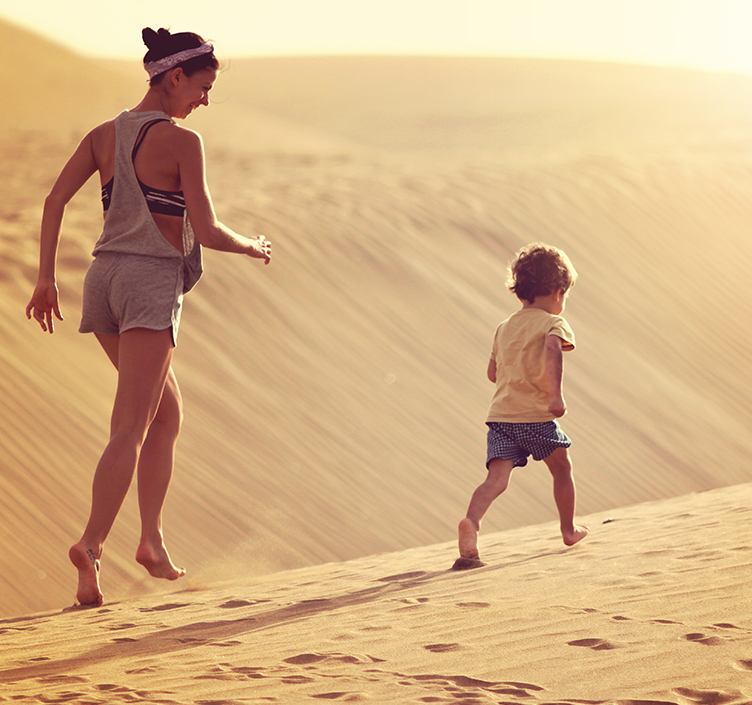 Mother and child running through the dessert
