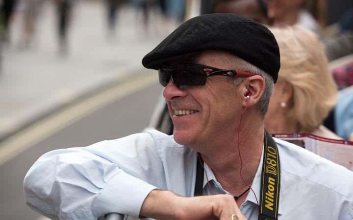 Man on Dublin bus tour listening to digital commentary