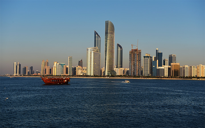 Traditional Arabian dhow boat cruising the Abu Dhabi skyline