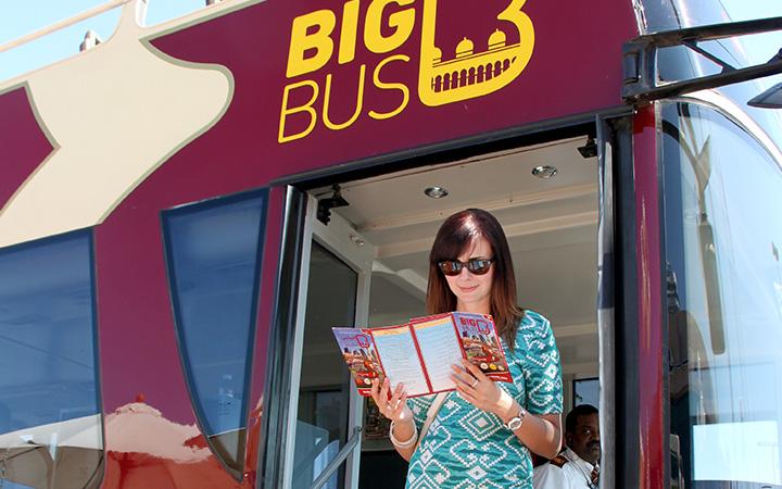 Frau mit Stadtplan steigt auf Abu Dhabi Bustour aus