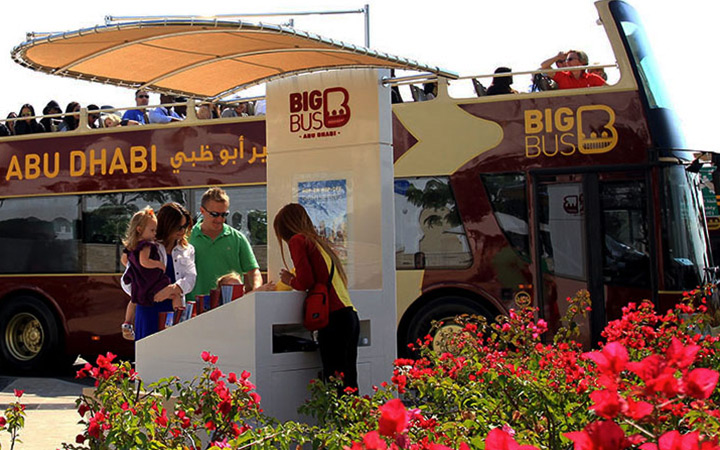 Family at Big Bus Tours kiosk with bus in background