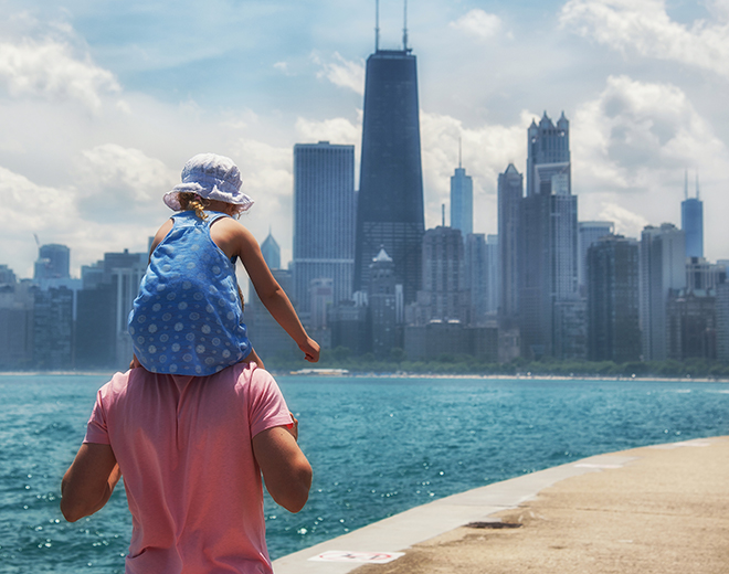 Child sat on dad's shoulders looking out the Chicago skyline