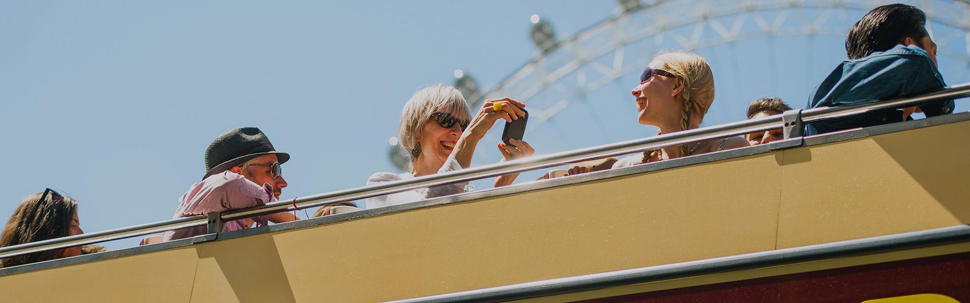 Passengers on London bus tour by London Eye