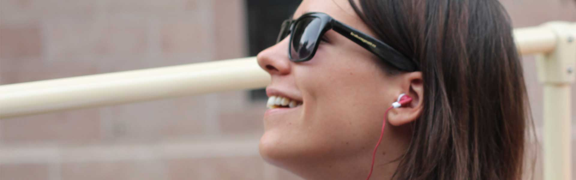 Woman in sunglasses listens to Big Bus Tours pre-recorded commentary via red headphones