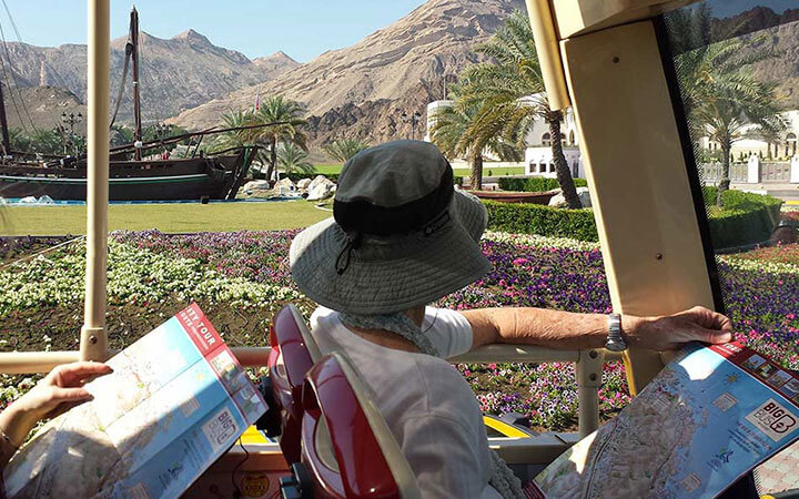 Passenger sitting in shade on Big Bus Tours Muscat top deck