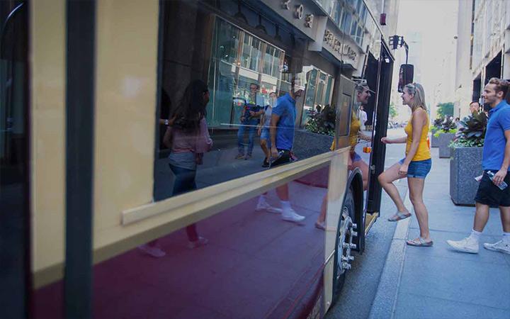 Kunden sprechen mit einem Mitglied des Teams von Big Bus Tours