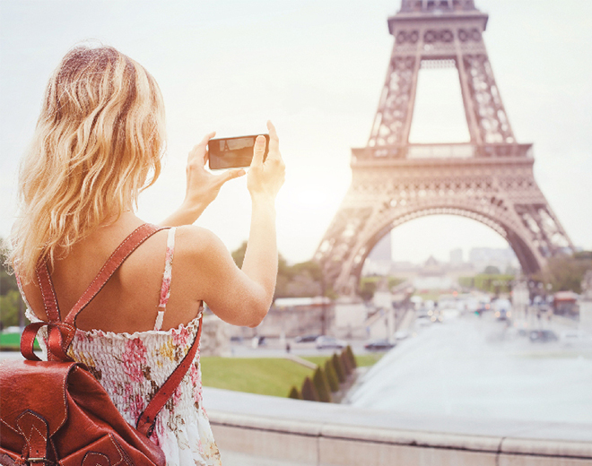 Lady taking a picture of the Eiffel Tower