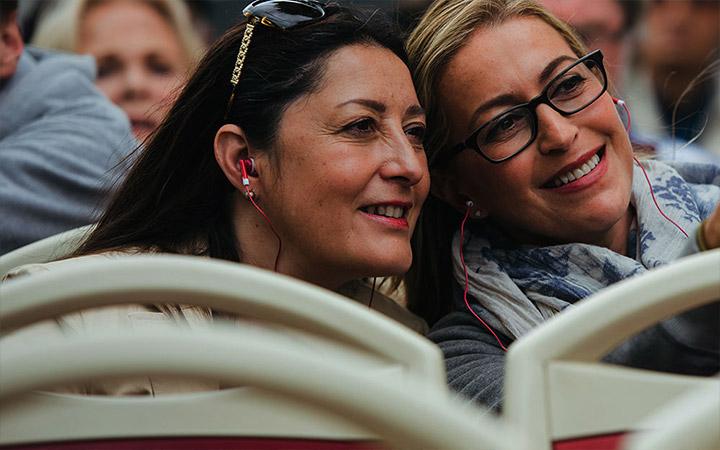 Dos mujeres que sonríen subiendo a un tour de Big Bus Tours en Roma