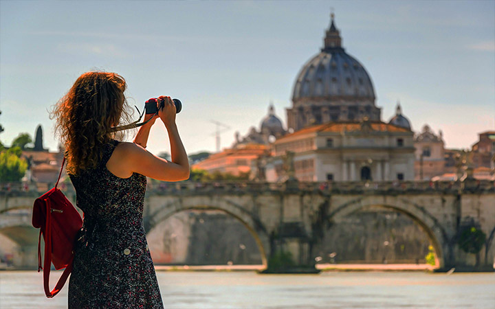 A woman takes a picture of St. Peter's Basilica in Rome