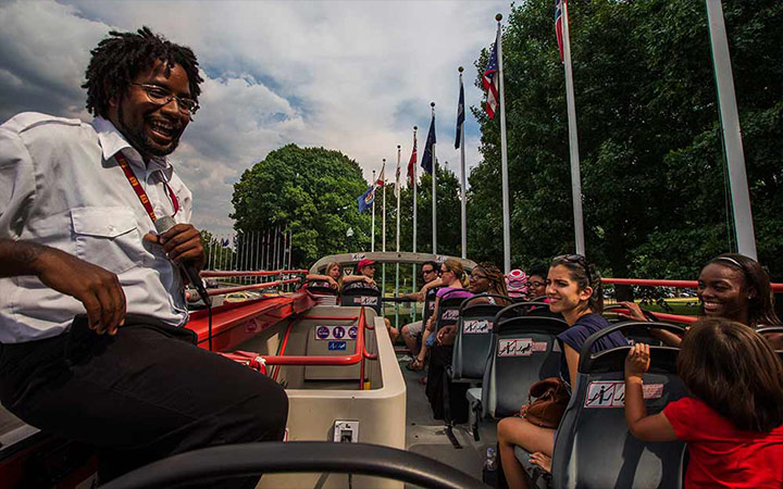 Guide entertaining passengers on top deck of Big Bus