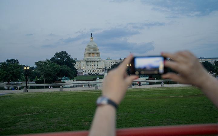Person nimmt mit dem Smartphone ein Foto vom Weißen Haus auf